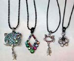 Pendant, necklace accessory outley distributes China import jewelry. Fun cubic zirconia pendants in an assortment of designs hanging from black beaded necklace