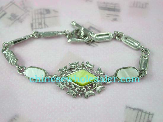 Online silver plated wholesale fashion jewelry. Pale light green seashell embedded loosely connected long strip forming fashion bracelet, toggle clasp for closure.