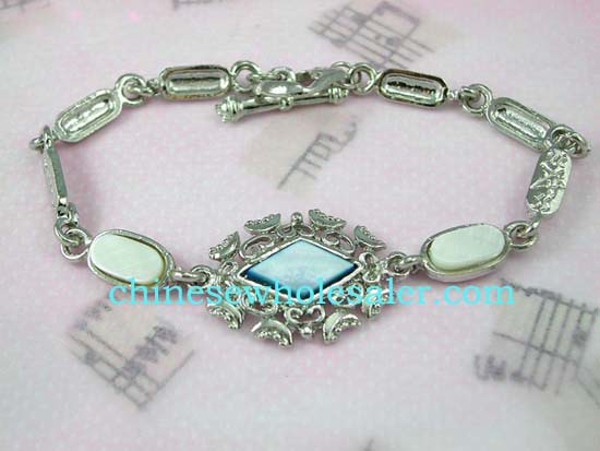 Fashion jewelry bracelet supplied wholesale from importinga agent. Light blue, diamond shaped center with  fancy design around connected by seashell inlaid in oval shaped chains. Toggle clasp for closure.
