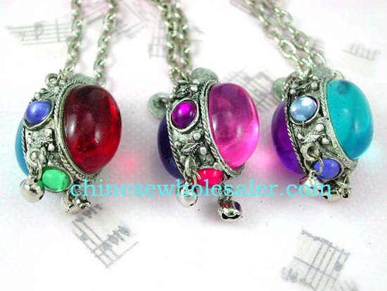 Costume jewelry distributed online from wholesale manufacturing company. Silver plated chian holds double backed colored gemstones set in oval shaped pendant frame with four smaller stones embedded in and two bells dangling below..