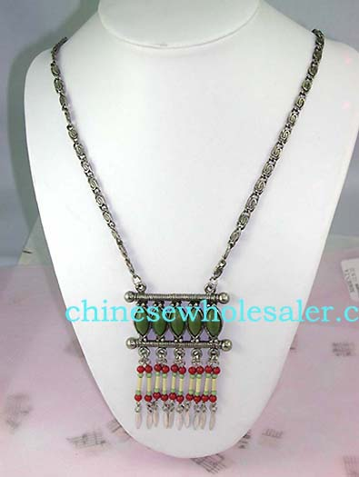 Exotic wholesale fashion jewelry store supplying Tibetan style dangling necklace with green cats eye shaped beads above columns of red, white, and light green beads with feather designed stone hanging below...