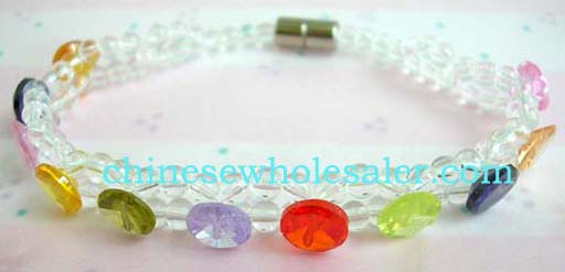 jewelry exporting agent distributing made in China bracelets. Clear double string beaded bracelet with multi colored rhinestones gems inlaid throughout. Attaches by screw-up clasp.