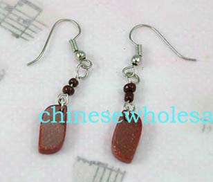 China costume jewelry products for export at wholesale prices. Silver plated costume earrings hanging on fish hooks for piercings. Two red beads are located above large read rectangular stone.