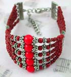 China wholesale colored beaded jewelry gifts supplied online. Fashion bracelet with five small red beaded strings each holding decorated silver beads and a large red bead in center.