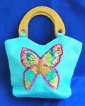 Wholesale hand bag products supplied by China manufacturer. Blue canvas fabric with sequins and wooden handle handbag motif. Butterfly feature in sparkle chips and thread work design with zipper closure and inner zipper pocket